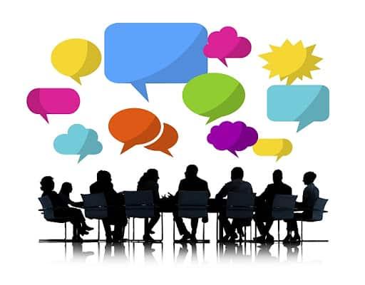 Obrazek przedstawia grafikę siedmiu osób siedzących przy stole konferencyjnym. Nad nimi unoszą się różnokolorowe dymki świadczące o tym że trwa żywa dyskusja.