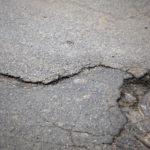 Obrazek przedstawia popękaną nawierzchnię ulicy asfaltowej