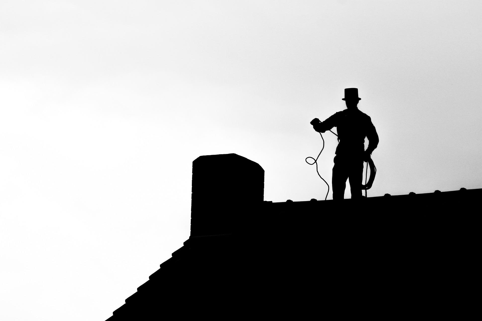 Obrazek przedstawia kominiarza na dachu przy kominie w kolorze czarnym na jasnoszarym tle